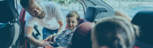 Father buckling children into car seats
