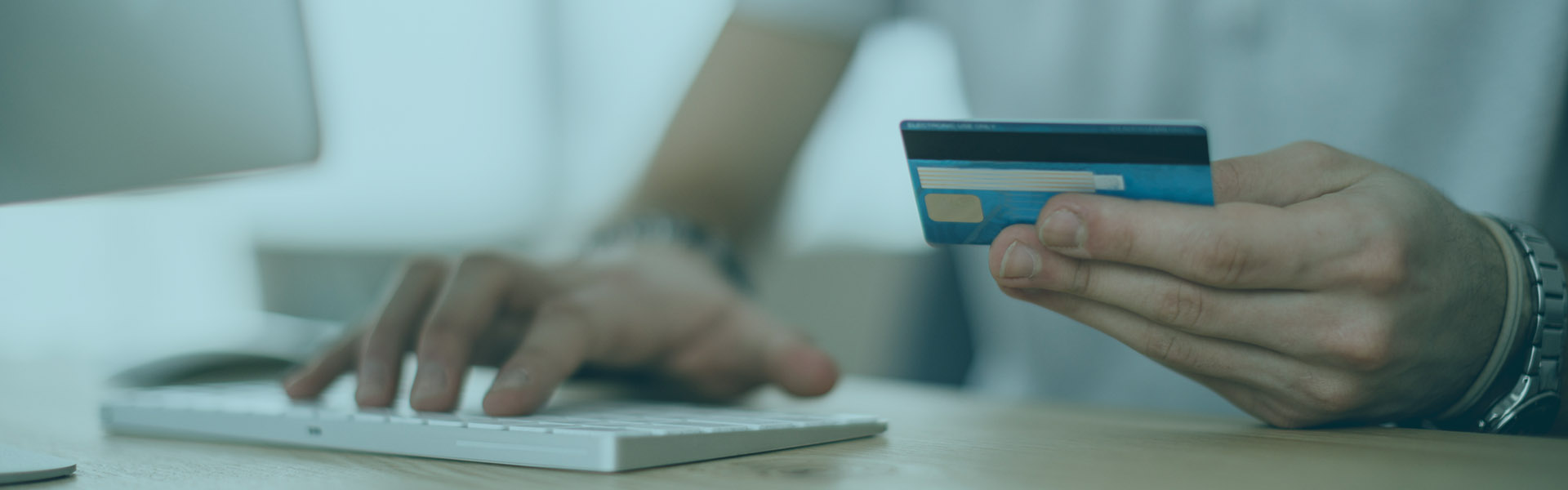 Man on Computer holding Debit Card