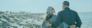 Gold Savings | Senior couple walking on beach