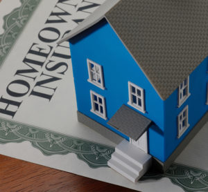 Homeowners Insurance blue house sitting on top of Insurance Certificate
