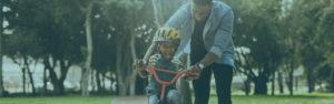 Father teaching son to ride bike