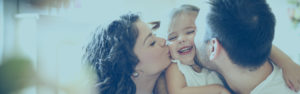 Share Savings Hero | Family kissing small child