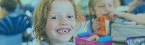Youth Savings   Child smiling at camera, missing teeth