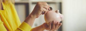 Putting money into piggy bank
